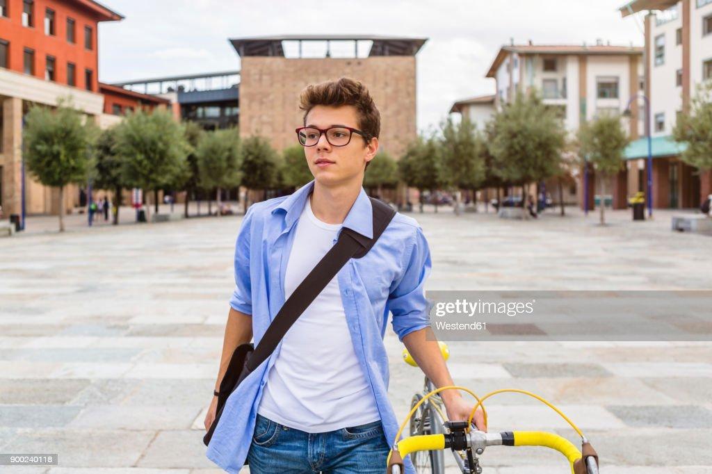 Portrait of young man pushing his bike : Stock Photo