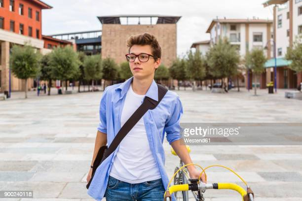 Portrait of young man pushing his bike