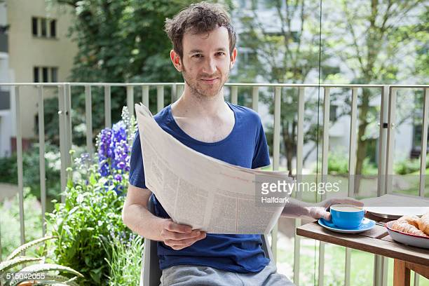 Portrait of young man reading newspaper while having coffee at porch
