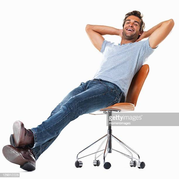 portrait of young man relaxing on chair with hands behind head and smiling against white background - legs crossed at ankle stock pictures, royalty-free photos & images