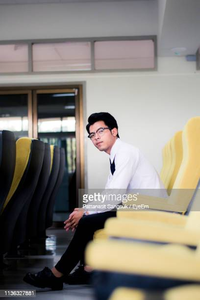 portrait of young man relaxing on seat in office - pattanasit stock pictures, royalty-free photos & images