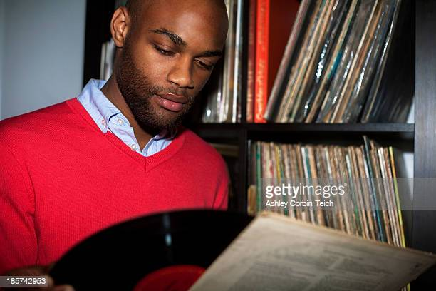 Portrait of young man removing vinyl record from sleeve