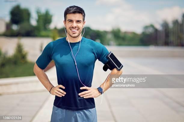 portret van jonge mens die in een stad na looppas rust - sportsperson stockfoto's en -beelden