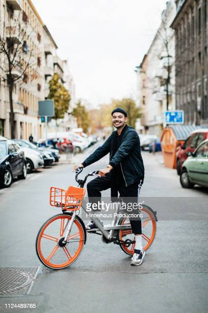 portrait of young man riding city bike - fahrrad stock-fotos und bilder