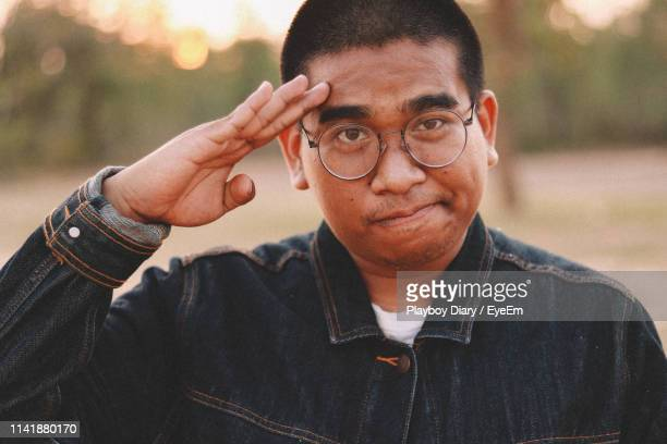 portrait of young man saluting against defocused background - saluting stock pictures, royalty-free photos & images