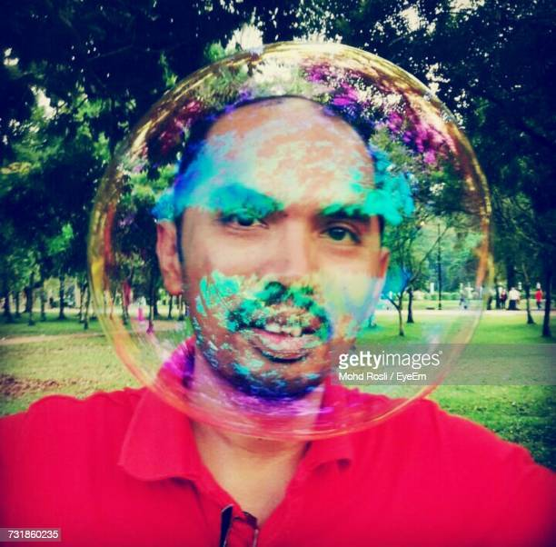 Portrait Of Young Man Seen Through Soap Bubble At Grassy Field