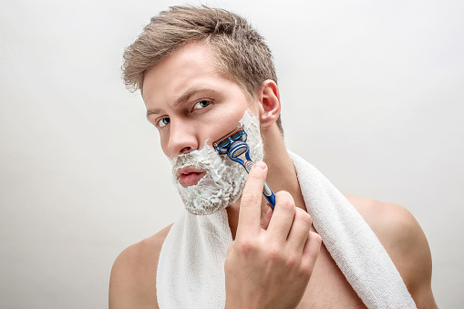 Portrait of young man shaving. He has white foam on beard. Guy is serious and concentrated. Isolated on white background. 1080201066