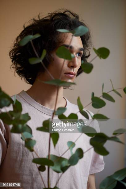Portrait of young man shot through green foliage