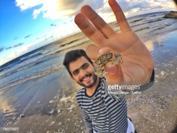 Portrait Of Young Man Showing Crab While Standing At Beach