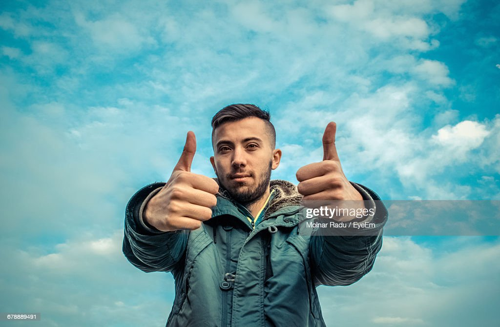 Portrait Of Young Man Showing Thumbs Up Sign Against Cloudy Sky : Stock Photo
