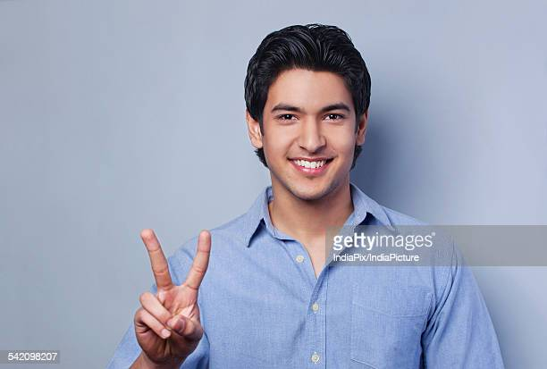 Portrait of young man showing V-sign