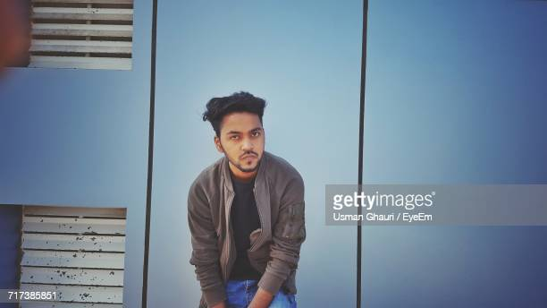 portrait of young man sitting against blue wall - only young men stock pictures, royalty-free photos & images