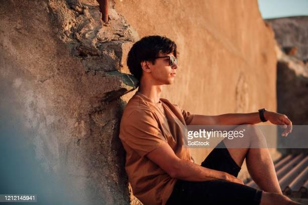verticale du jeune homme s'asseyant contre le mur au coucher du soleil - short photos et images de collection