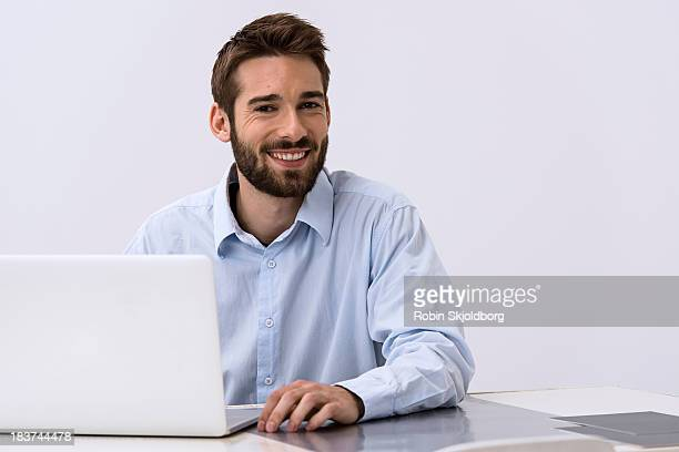 Portrait of young man sitting at desk with laptop