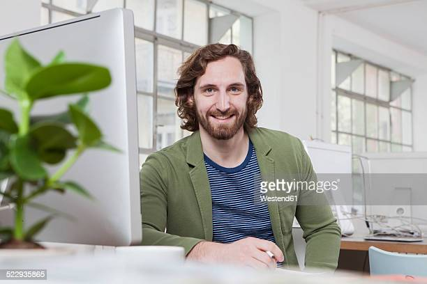 Portrait of young man sitting at his desk in a creative office