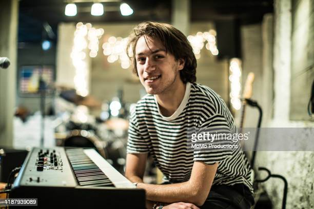portrait of young man sitting at keyboard - pianist front stock pictures, royalty-free photos & images