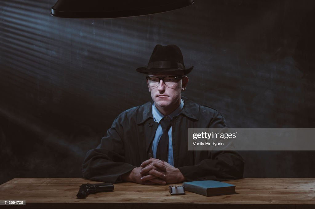 Portrait of young man sitting at table with gun against black wall : Stock Photo