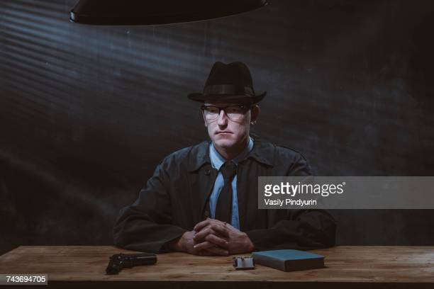 Portrait of young man sitting at table with gun against black wall