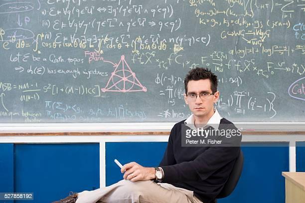 Portrait of young man sitting by blackboard