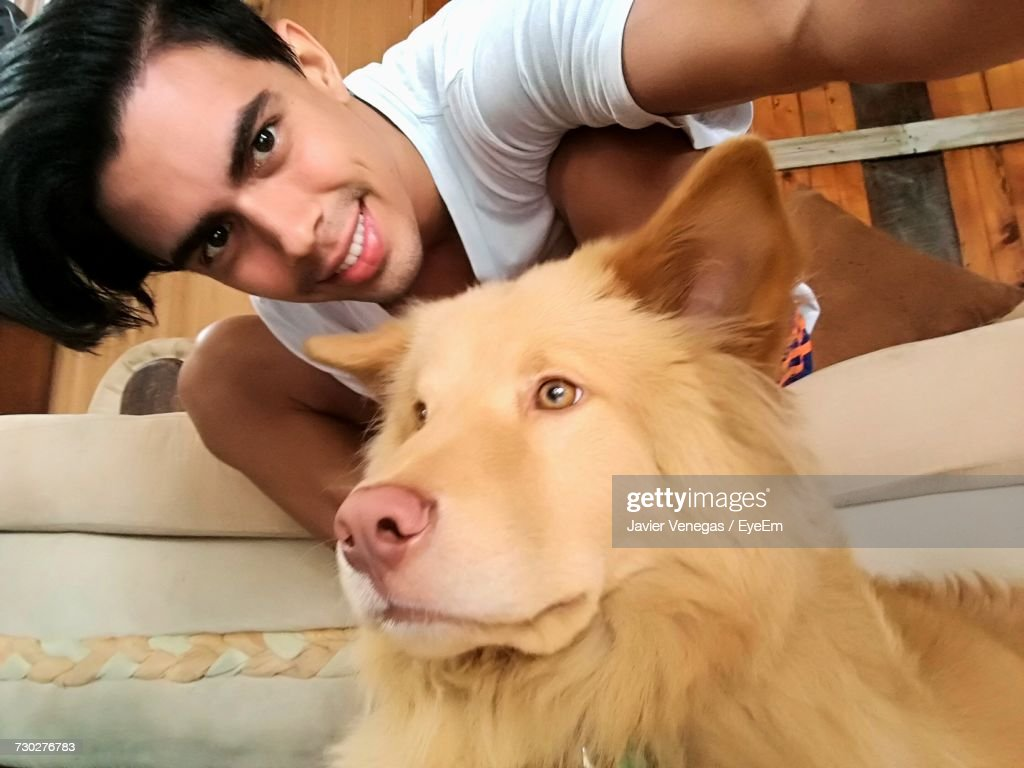 Portrait Of Young Man Sitting By Dog At Home Stock Photo