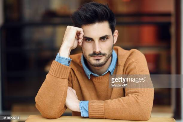 portrait of young man sitting in a coffee shop - one man only stock pictures, royalty-free photos & images