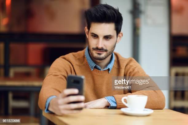 portrait of young man sitting in a coffee shop using cell phone - só um homem - fotografias e filmes do acervo