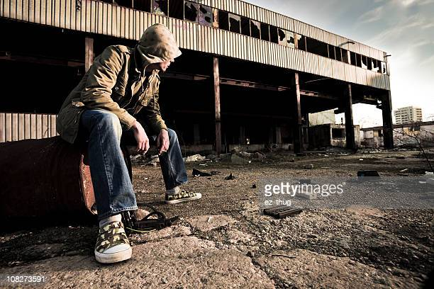 portrait of young man sitting near abandoned building - ghetto trash stock pictures, royalty-free photos & images
