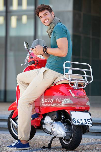 Portrait of young man sitting on a scooter and text messaging
