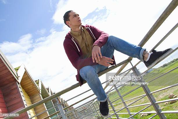 portrait of young man sitting on beach hut fence - blyth northumberland stock pictures, royalty-free photos & images