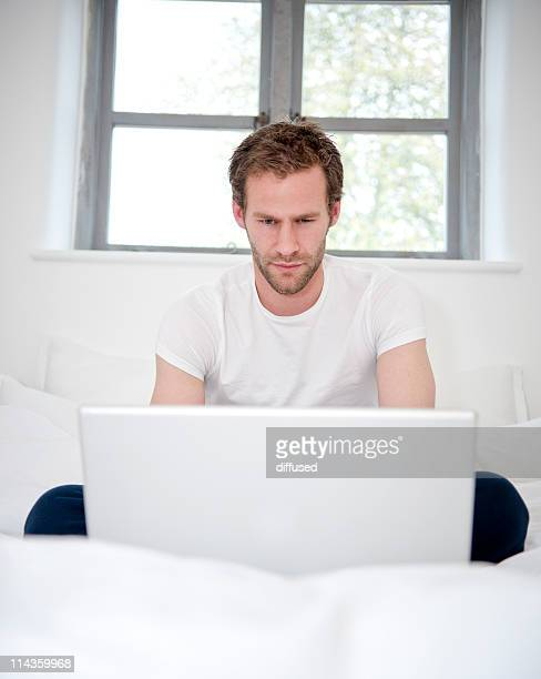 portrait of young man sitting on bed working with laptop computer
