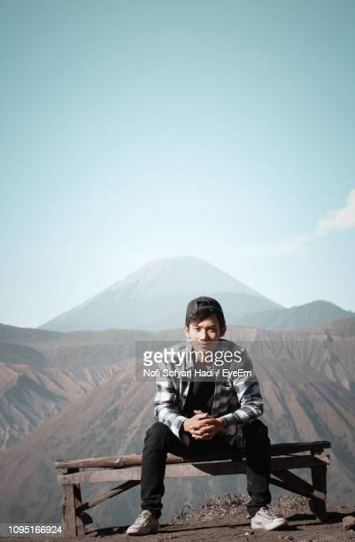Portrait Of Young Man Sitting On Bench Against Mountains During Sunny Day