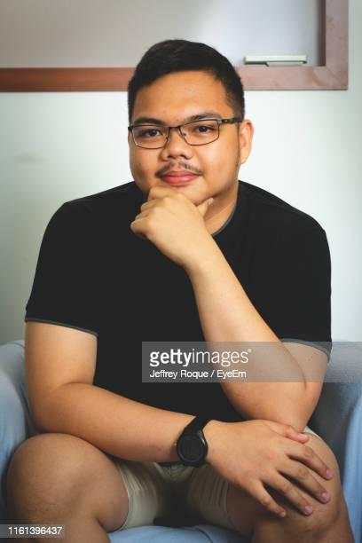 portrait of young man sitting on chair at home - jeffrey roque stock photos and pictures