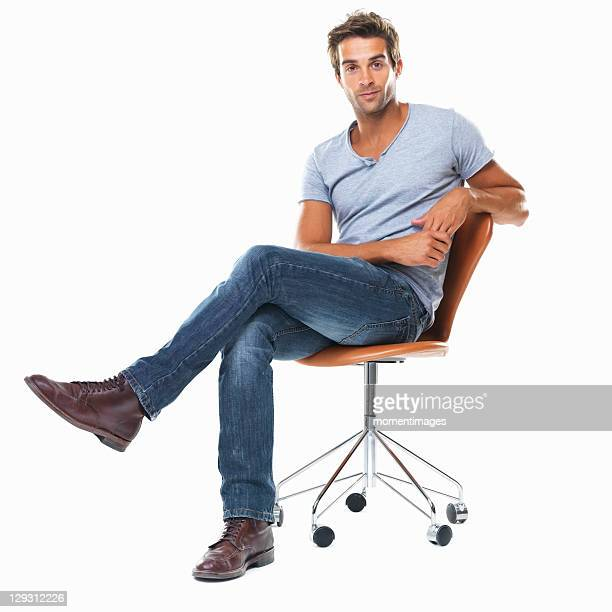 portrait of young man sitting on chair with legs crossed against white background - cadeira - fotografias e filmes do acervo