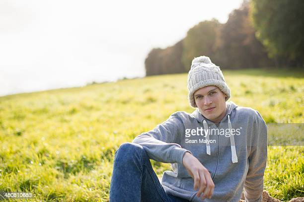 Portrait of young man sitting on grass wearing knit hat