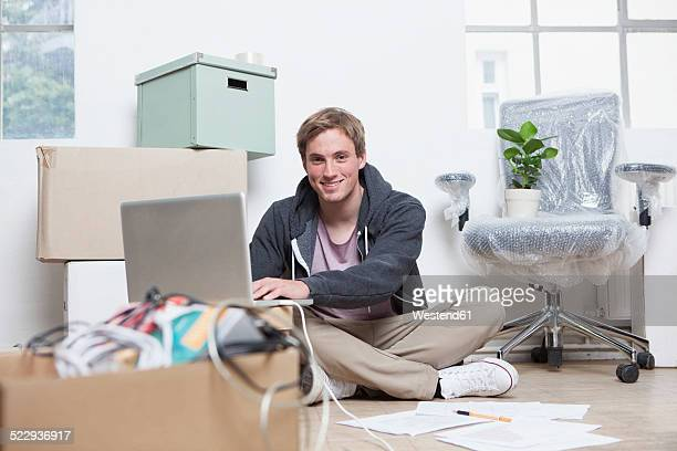 Portrait of young man sitting on ground between cardboard boxes in an office using his notebook
