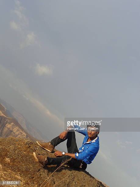 Portrait Of Young Man Sitting On Rock Against Sky