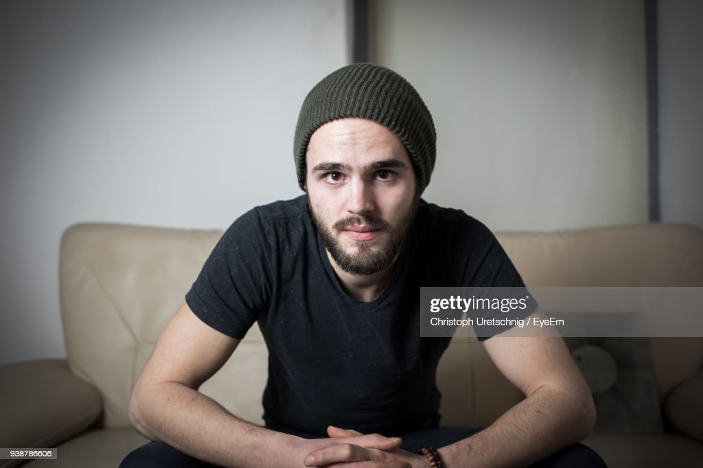 Portrait Of Young Man Sitting On Sofa At Home : Stock Photo