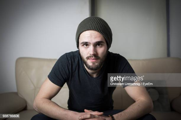 portrait of young man sitting on sofa at home - knit hat stock pictures, royalty-free photos & images