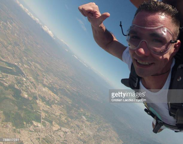 Portrait Of Young Man Skydiving Over Landscape