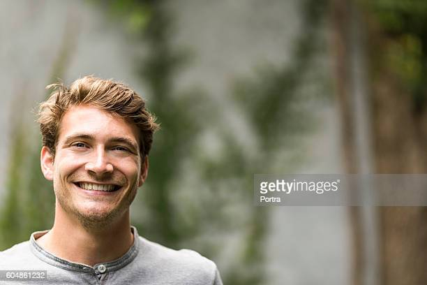 Portrait of young man smiling in yard