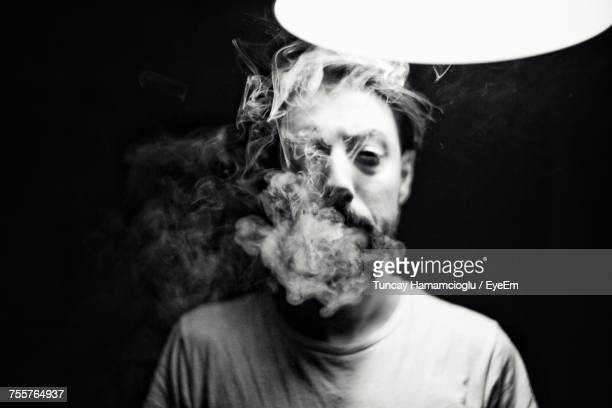 Portrait Of Young Man Smoking Against Black Background