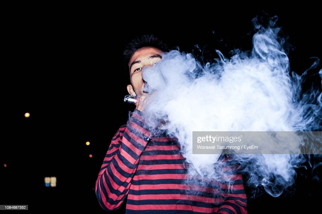 Portrait Of Young Man Smoking Electronic Cigarette At Night : Stock Photo