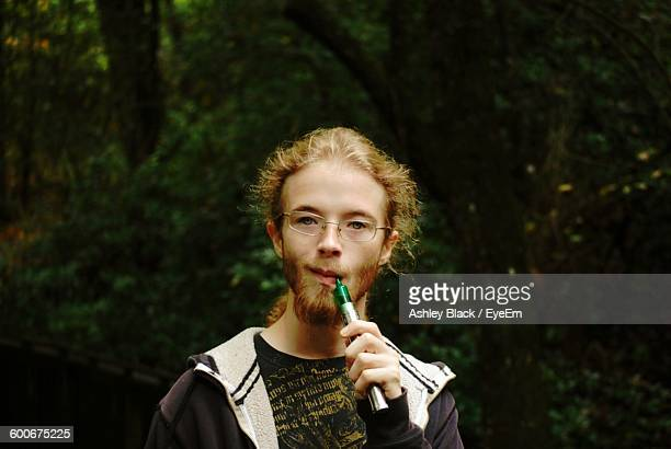 Portrait Of Young Man Smoking Electronic Cigarette While Standing Against Trees