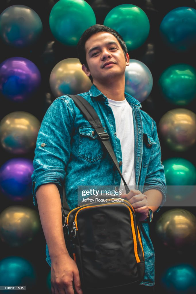 Portrait Of Young Man Standing Against Balls : Stock Photo
