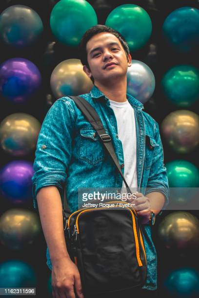 portrait of young man standing against balls - jeffrey roque stock photos and pictures
