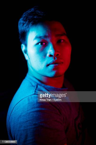portrait of young man standing against black background - portrait blue background stock pictures, royalty-free photos & images