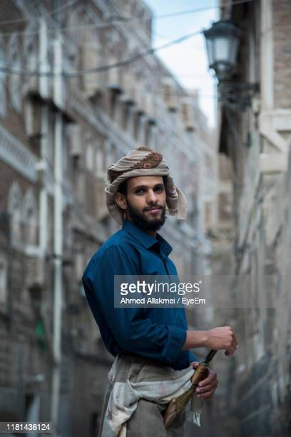 portrait of young man standing against building in city - yemen stock pictures, royalty-free photos & images