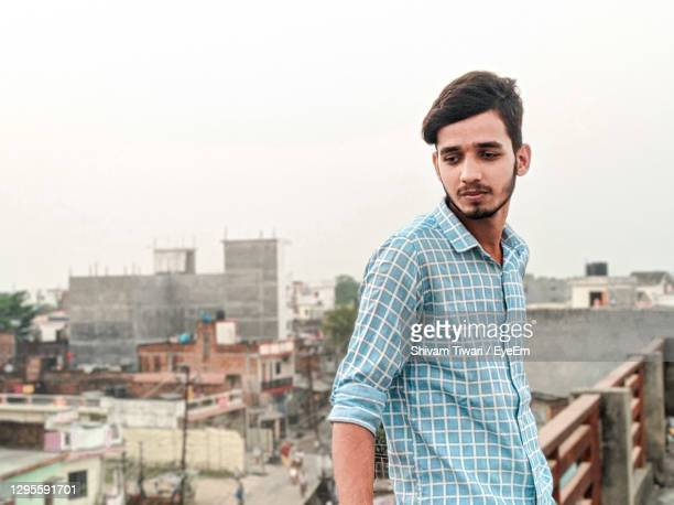 portrait of young man standing against cityscape - printed sleeve stock pictures, royalty-free photos & images