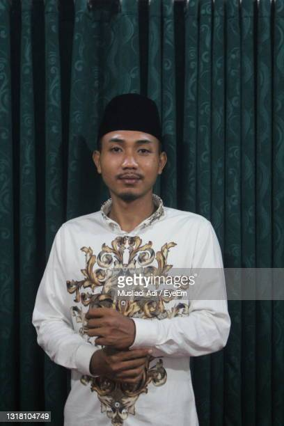 portrait of young man standing against curtain - indonesia stock pictures, royalty-free photos & images