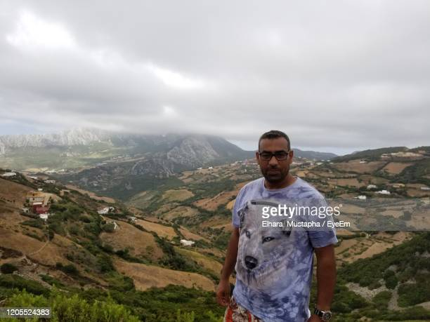 portrait of young man standing against mountain and sky - homme maghrebin photos et images de collection